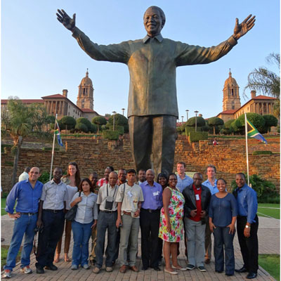 Delegates pose in front of the statue of former president Nelson Mandela at the Union Buildings in Pretoria.
